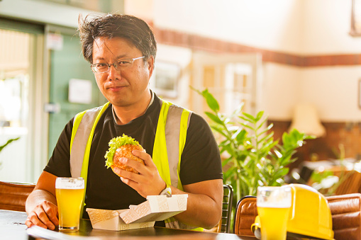 Workman wearing high visibility clothes eating a healthy hamburger after work